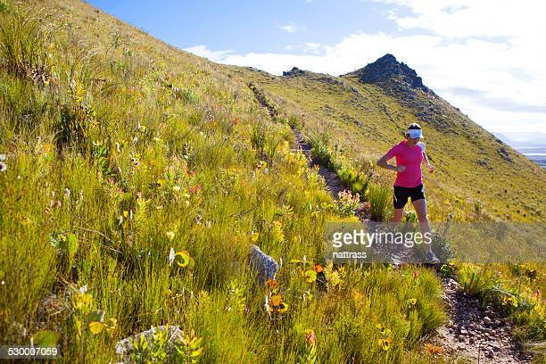Female running strong down a mountain trail.