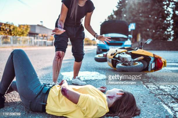 female running to check her friend hurt badly in motorcycle accident - motorcycle accident stock pictures, royalty-free photos & images