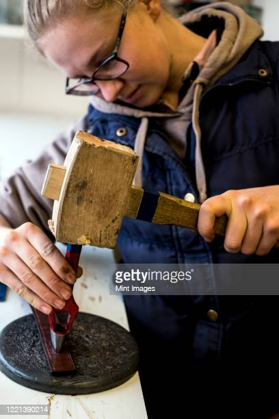 female saddler standing in workshop, using hand tool and wooden mallet, punching holes into leather strap. - strap stock pictures, royalty-free photos & images