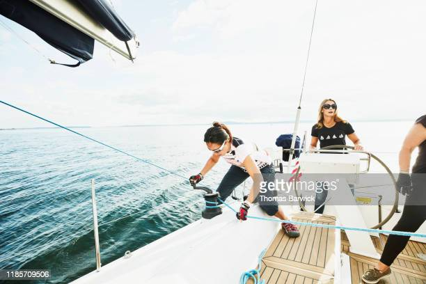 female sailboat crewmember trimming sail with winch during sail on summer evening - sports team stock pictures, royalty-free photos & images