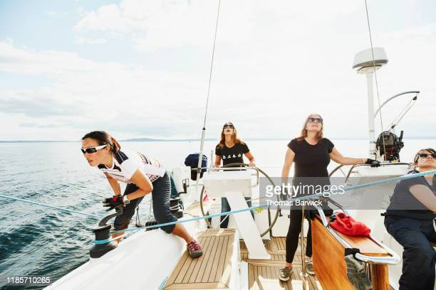 female sailing team preparing to tack while training together - sportkleding stock pictures, royalty-free photos & images