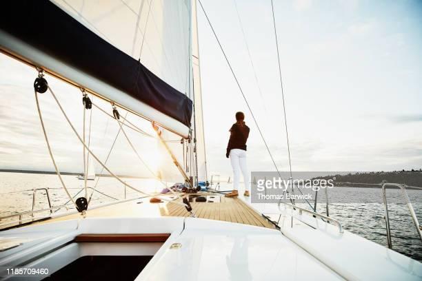 female sailor standing on foredeck of sailboat watching sunset on summer evening - luxus stock-fotos und bilder