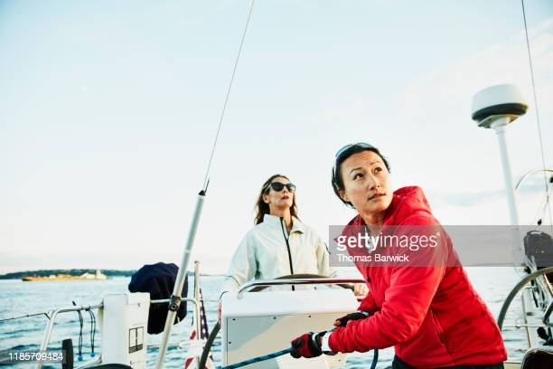 female sailor trimming sail during race on summer evening - sportkleding stock pictures, royalty-free photos & images