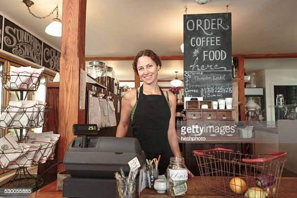 female sales assistant checking out shopping in country store cafe - heshphoto stock-fotos und bilder