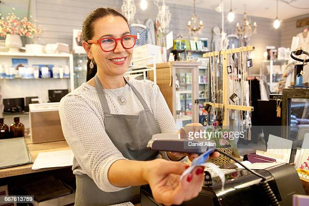 female sales assistant taking credit card payment at checkout in gift shop - ギフトショップ ストックフォトと画像