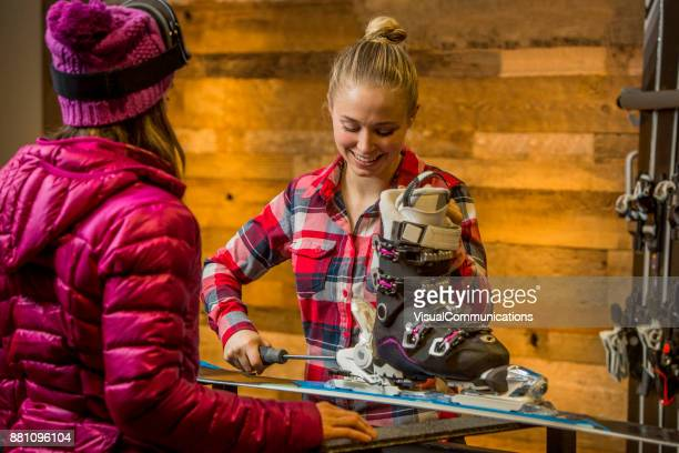 Female Sales Assistant tuning up skis for customer.