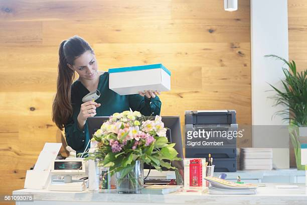 Female sales assistant using barcode reader on shoe box in shoe shop