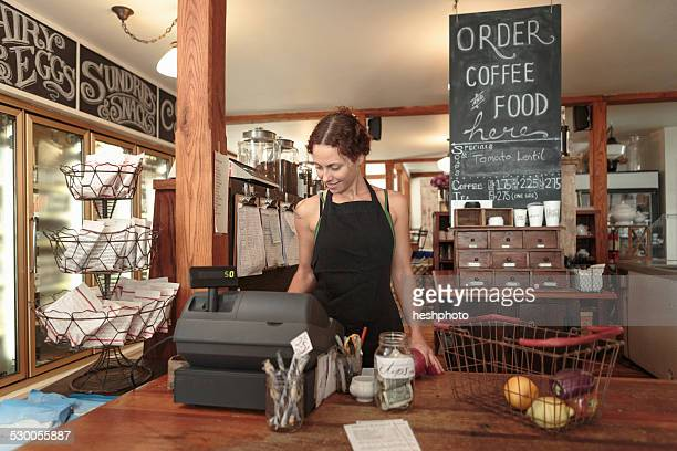 female sales assistant using check out till in country store cafe - heshphoto stock pictures, royalty-free photos & images