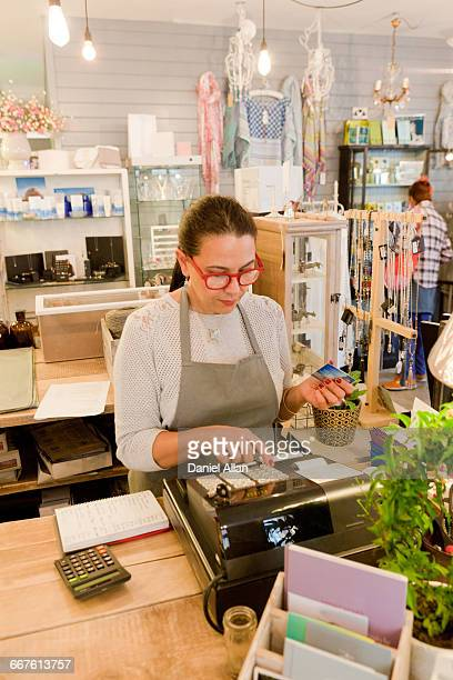 female sales assistant using till at checkout in gift shop - gift shop stock pictures, royalty-free photos & images