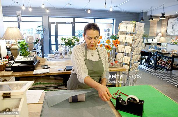 female sales assistant wrapping candle at checkout in gift shop - gift shop stock pictures, royalty-free photos & images