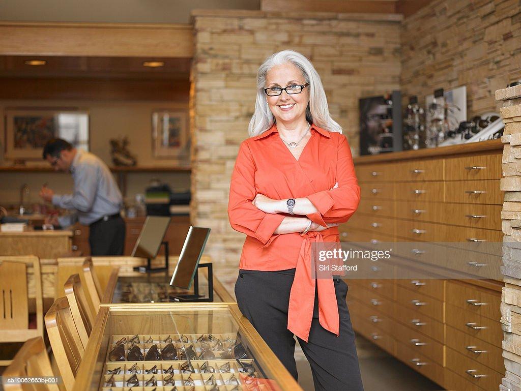 Female sales clerk standing in eyeglass store, portrait, customer in background : Stock Photo