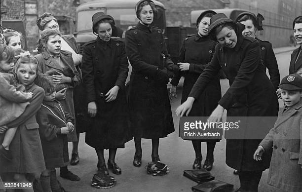 Female Salvation Army cadets singing songs with actions with a group of children at East Street Market Camberwell south London 1950 The market is...