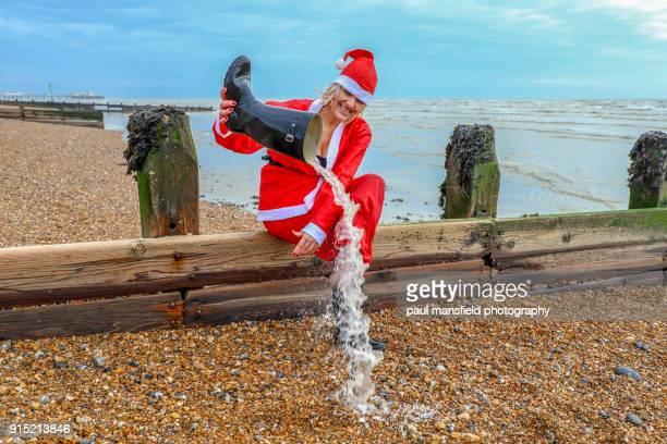 female santa claus at the seaside - weihnachtsfrau stock-fotos und bilder