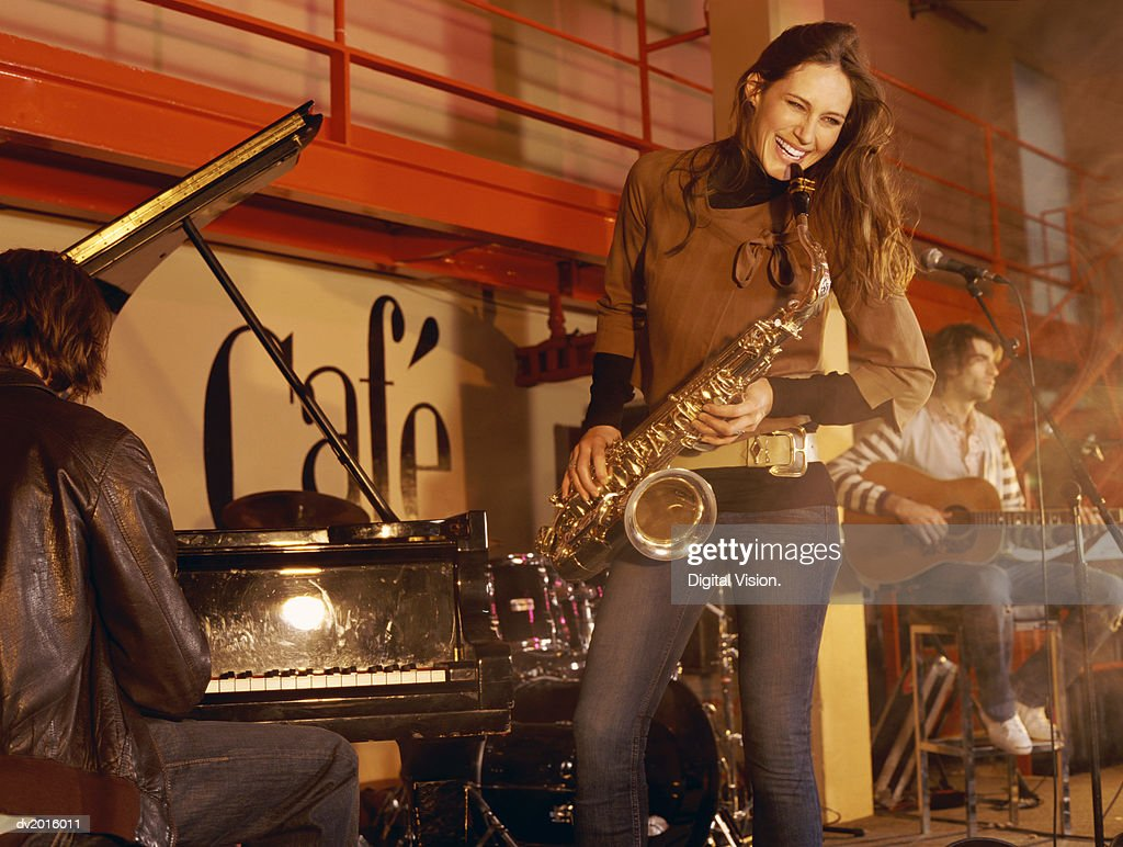Female Saxophonist Performs on Stage With a Pianist and Guitarist : Stock Photo