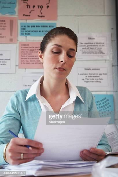 Female schoolteacher sitting at desk, reading paperwork