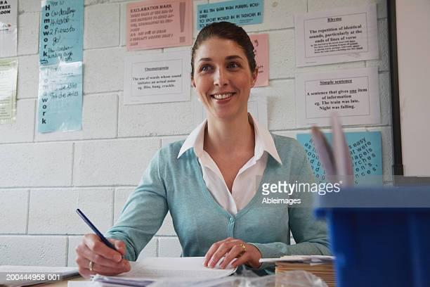 Female schoolteacher sitting at desk, smiling