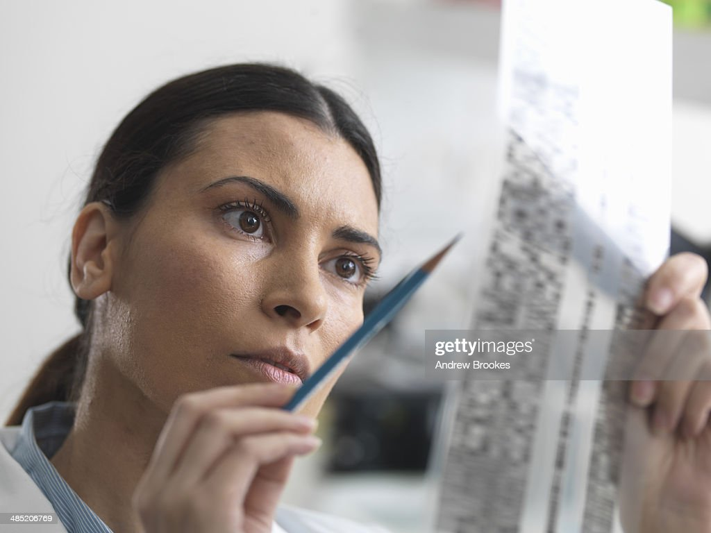 Female scientist examining DNA gel in laboratory for genetic research : Stock Photo