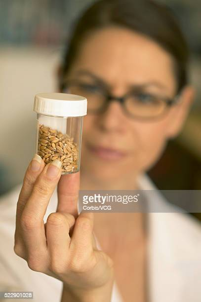 Female scientist examining plant seeds in a jar