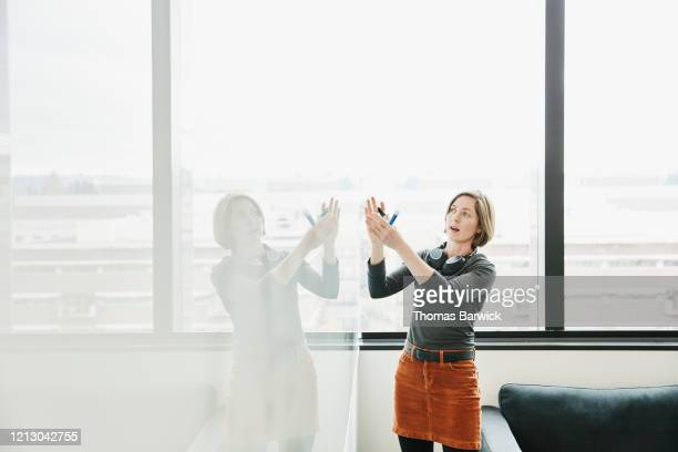 female scientist explaining project data at whiteboard in conference room - gesturing stock pictures, royalty-free photos & images