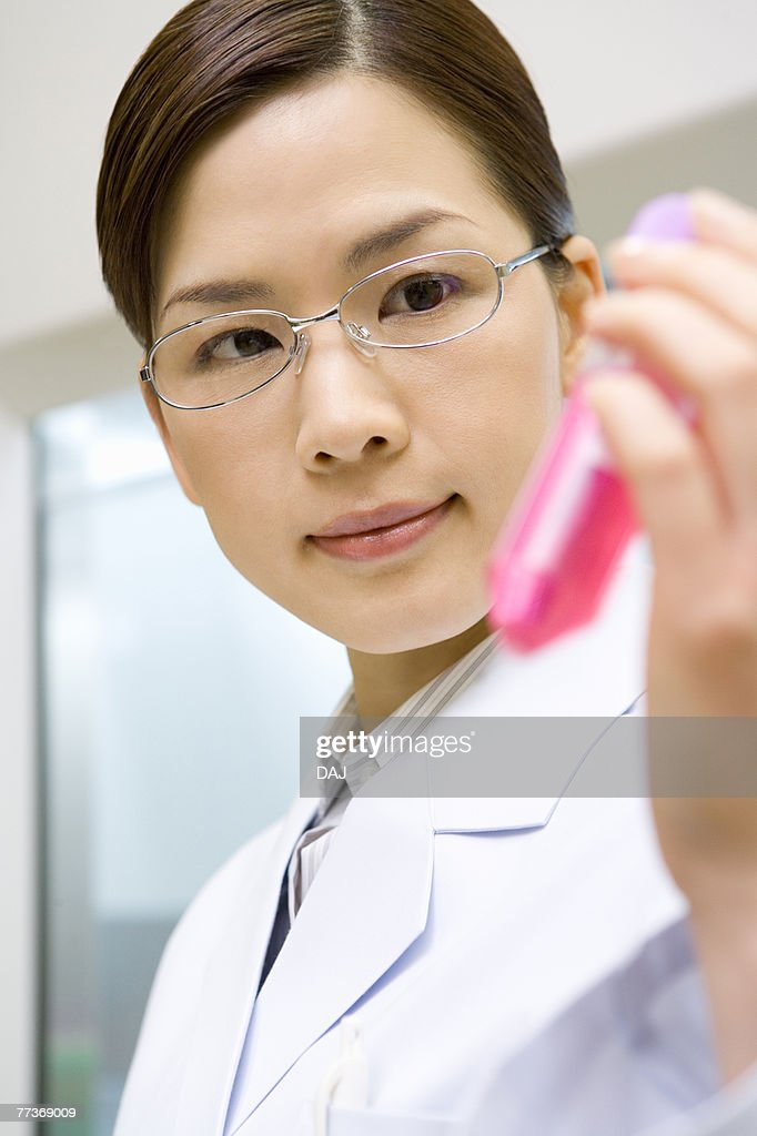 Female scientist holding and looking at micro test tube with liquid, front view : Photo