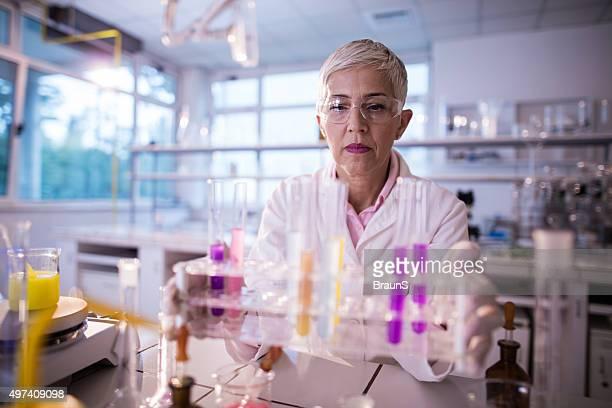 mulher cientista exploração grande grupo de multi-coloridas tubos de ensaio. - bioquímico imagens e fotografias de stock