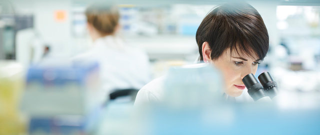 female scientist in a busy research lab 923038872