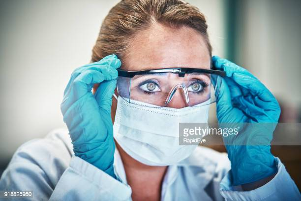 Female scientist in mask and goggles stares seriously
