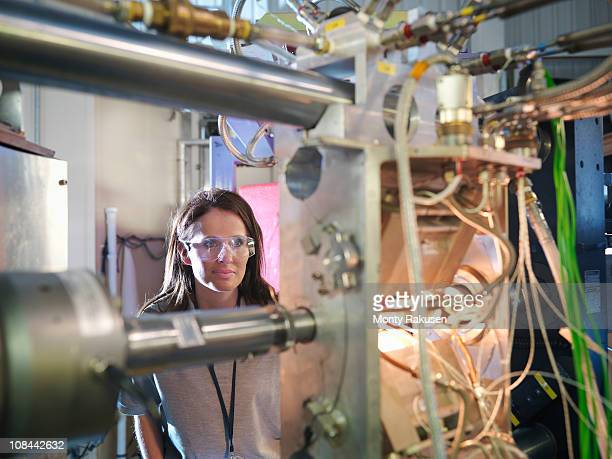 female scientist inspects particle accelerator target - physics stock pictures, royalty-free photos & images