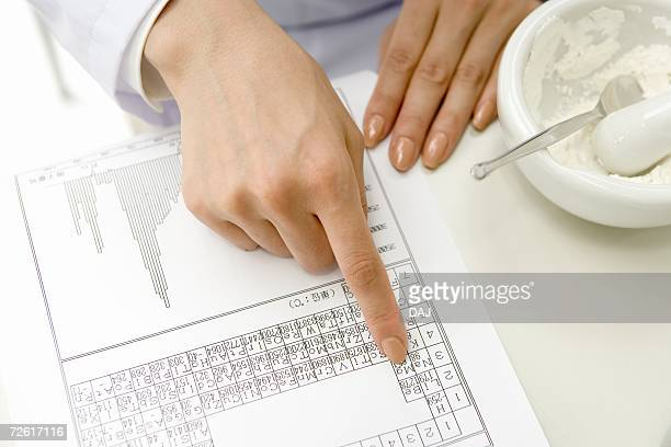 female scientist looking and pointing on the periodic table of the elements, mortar and pestle on table, high angle view - periodic table stock pictures, royalty-free photos & images
