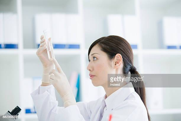 Female scientist looking at test tube, side view