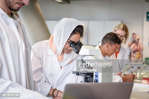 Female scientist looking through microscope lens at medical sample