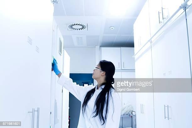 female scientist opening sample cupboard in laboratory - sigrid gombert stock-fotos und bilder