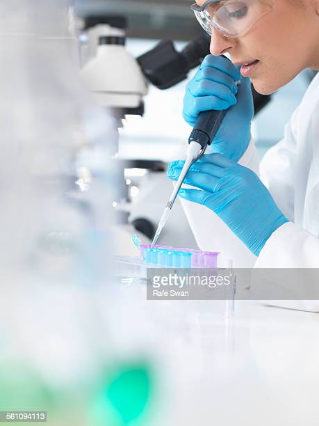 Female scientist pipetting sample into a vial for analytical testing in a laboratory