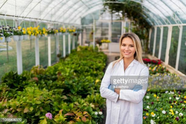 female scientist standing in greenhouse - agronomist stock pictures, royalty-free photos & images