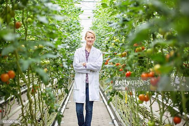 Female scientist standing in greenhouse