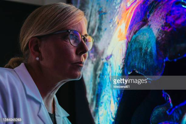 female scientist studying about human brain with nerve fiber while standing at laboratory - research stock pictures, royalty-free photos & images