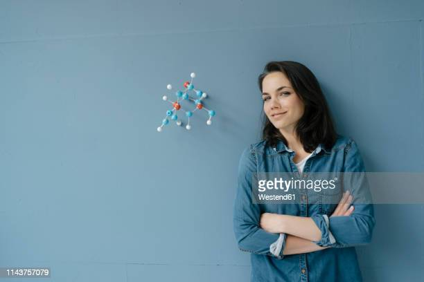 female scientist studying molecule model, looking for solutions - woman blue background stock pictures, royalty-free photos & images