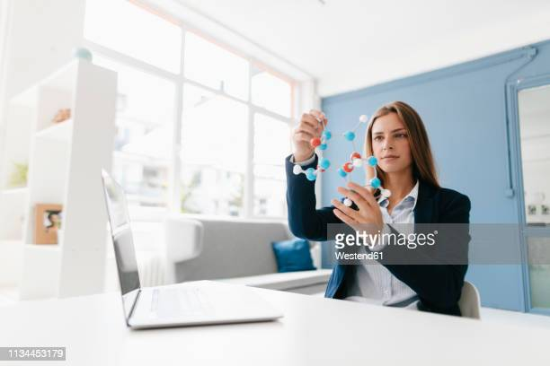female scientist studying molecule model - genetisk forskning bildbanksfoton och bilder