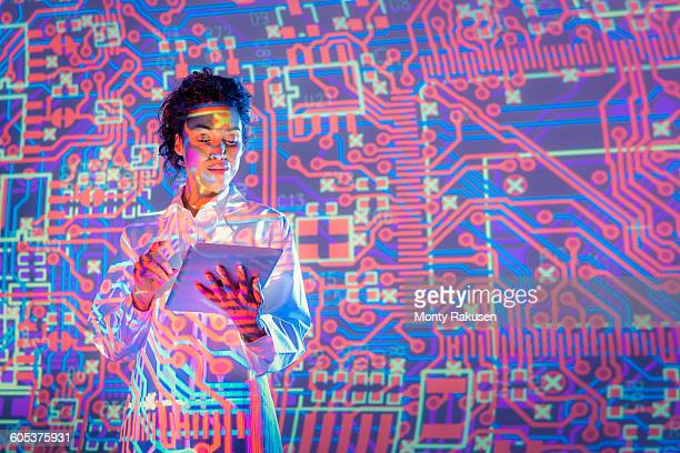 Female scientist using digital tablet with graphical electronic circuit projection