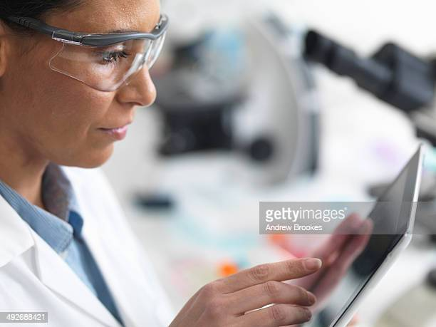Female scientist viewing test results on a digital tablet in lab