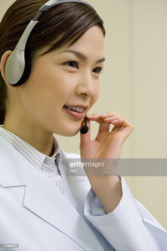 Female scientist wearing a headset, smiling, side view : Photo