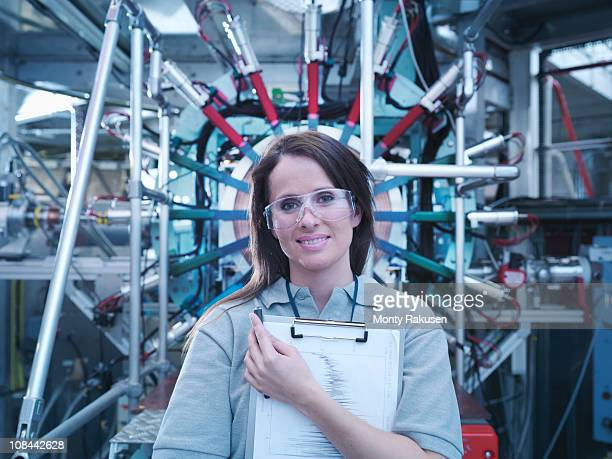 Female scientist with clipboard in front of particle accelerator