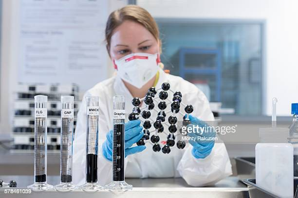 Female scientist with graphene nano material molecular model in graphene processing factory