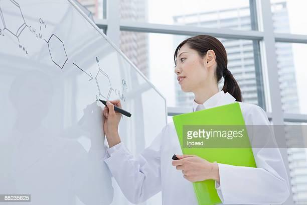 Female scientist writing down molecular structure