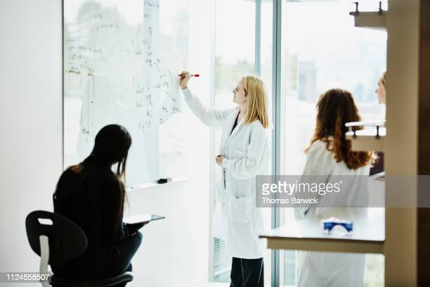 female scientist writing formula on white board while discussing project with colleagues - scienziata foto e immagini stock