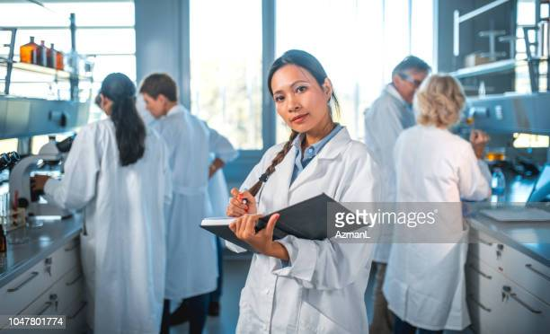 female scientist writing in diary with team in lab - scientist stock pictures, royalty-free photos & images