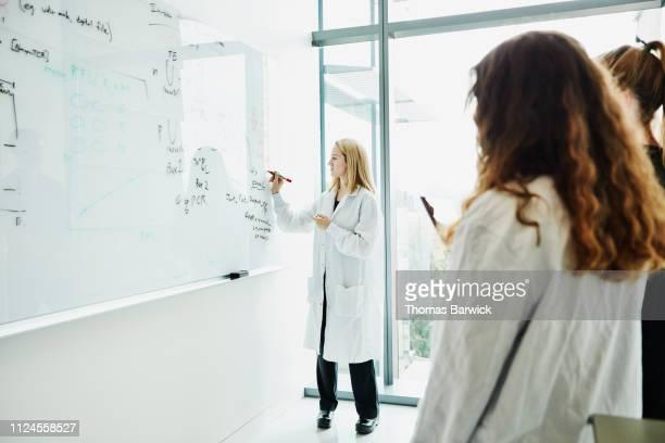 female scientist writing notes on white board in laboratory while discussing project with colleagues - scienziata foto e immagini stock