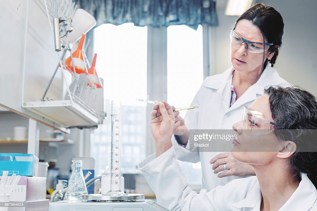 Female scientists analyzing chemical in laboratory : Stock Photo