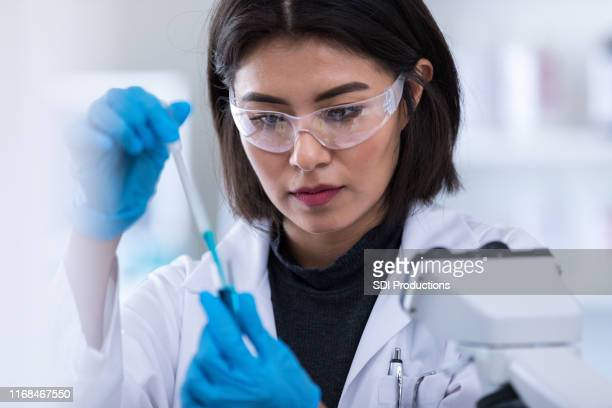 female scientists concentrates while preparing sample - microbiologist stock pictures, royalty-free photos & images