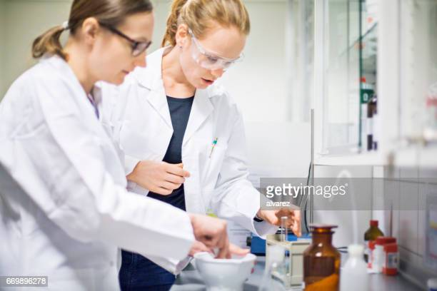 female scientists making medicine at laboratory - homeopathic medicine stock photos and pictures